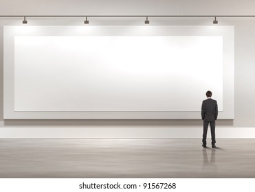 Business person standing near a blank  billboard