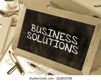 Business Solutions Handwritten by white Chalk on a Blackboard. Composition with Small Chalkboard on Background of Working Table with Office Folders, Stationery. Blurred Background. Toned Image.