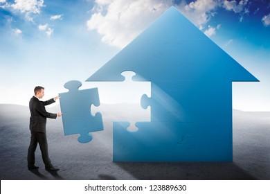 Businessman building a house jigsaw puzzle