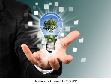 businessman hand holding a blub with tree inside