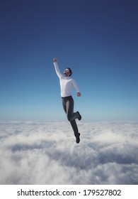Businessman hero flying over clouds