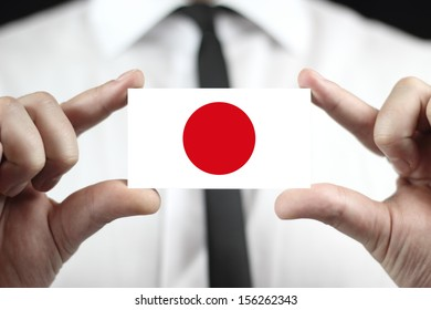 Businessman holding a business card with a Japan Flag
