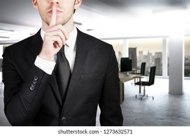 businessman in large clean office with finger on lips asking for silence 3d illustration