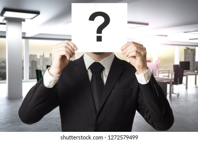 businessman in large modern office hides face behind sign question mark