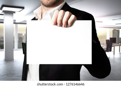 businessman in large modern office interior holding empty paper card - 3D Illustration
