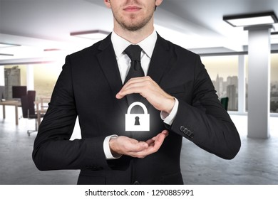 businessman in large modern office protecting lock symbol with his hands