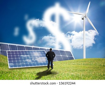 Businessman looking at dollar signs made of clouds in a field with solar panels and wind turbine
