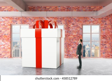 Businessman looking at huge present box in red brick interior with city view. 3D Rendering