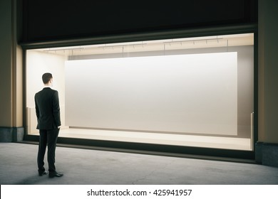 Businessman looking at showcase with blank banner at night. Mock up, 3D Rendering
