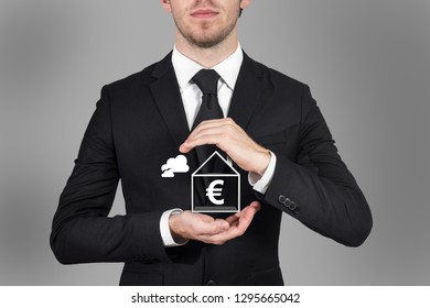 businessman protecting euro symbol in small home with his hands