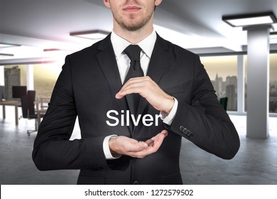 businessman protecting the word silver with his hands in empty office location