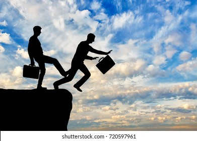Businessman stumbles on the leg of another businessman and falls into the abyss. The concept of risk and rivalry in business