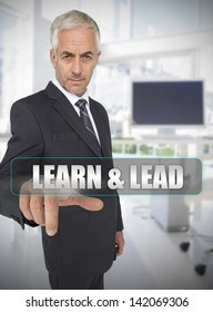 Businessman touching the term learn and lead in his office