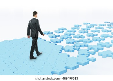 Businessman walking on abstract blue puzzle piece road. White background. Success concept. 3D Rendering