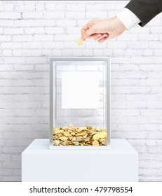 Businessperson hand putting coin into donation box with blank label. White brick wall background. Charity concept. Mock up, 3D Rendering