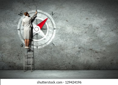 Businesswoman drawing compass with finger on wall standing on ladder
