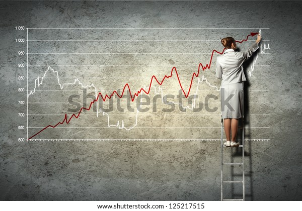 businesswoman standing on ladder drawing diagrams and graphs on wall
