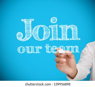 Businesswoman writing join our team on blue background with a chalk