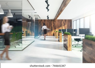Businesswomen in a nature style open space office environment with wooden walls, beds with grass and a row of computer tables. A conference room. 3d rendering mock up
