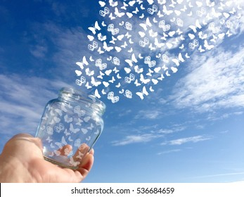 Butterflies coming out of a jar in a man's hand