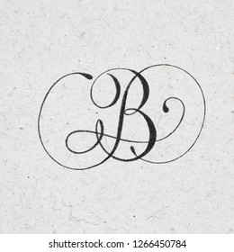 Calligraphic letter B with flourishes - ink bleed on kraft textured paper