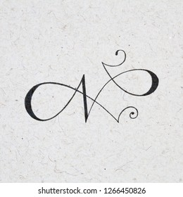 Calligraphic letter N with flourishes on kraft paper