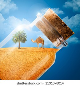 A camel and a palm tree in a bottle of sand. The desert in the bottle. A camel with a desert. Bottle with sand on a blue background. Bottle on a blue background. Traveling in the desert