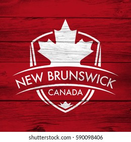 A Canadian province crest on a background of distressed barnboard. The shield features a maple leaf and the main text says New Brunswick, Canada.