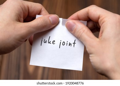 Cancelling juke joint. Hands tearing of a paper with handwritten inscription.