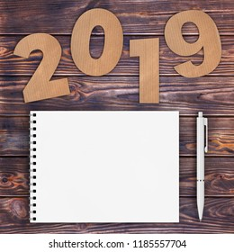 Cardstock Numbers 2019 Happy New Year Sign near White Spiral Paper Cover Notebook with Pen over wooden table background. 3d Rendering