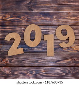 Cardstock Numbers 2019 Happy New Year Sign over wooden table background. 3d Rendering
