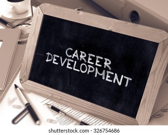 Career Development Handwritten by white Chalk on a Blackboard. Composition with Small Chalkboard on Background of Working Table with Office Folders, Stationery, Reports. Blurred, Toned Image.