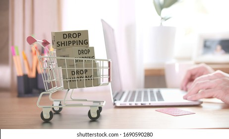 Cartons with DROPSHIPPING text fall in shopping cart after placing order by customer on the laptop. 3D rendering