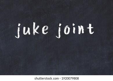 Chalk handwritten inscription juke joint on black desk