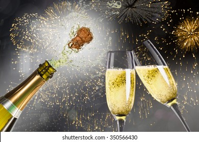 Champagne popping against colourful fireworks exploding on black background