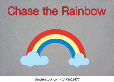 Chase the rainbow written in red text above a colorful rainbow in the clouds on an isolated grey textured background.