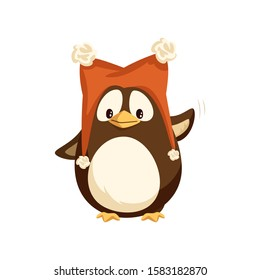 Cheerful standing penguin in funny hat with furry balls and waving hand. Animal in big red cap with pompons in flat style isolated on white raster
