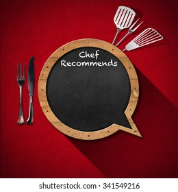 Chef Recommends - Blackboard Speech Bubble Shaped / Blackboard in the shape of speech bubble with text Chef Recommends with kitchen utensils on a red velvet background