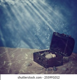 chest with coins under water