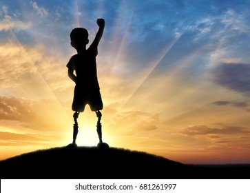 Children with disabilities concept. Happy disabled boy with a prosthetic leg standing on top of a hill at sunset