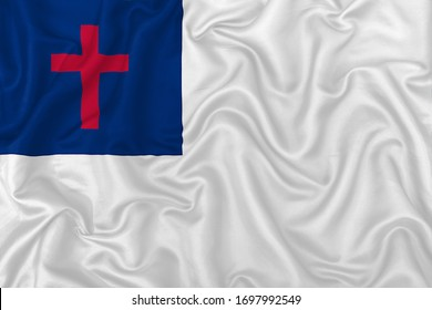 Christian ecumenical flag on wavy silk textile fabric background.