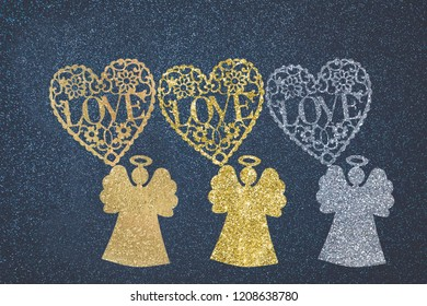 Christmas Angels and love greeting card. Three angels and hearts with love message made with shiny glitter brush