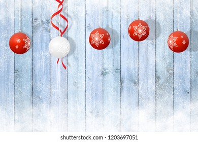 Christmas decoration, 4 red and 1 white balls on a blue snowy wooden background
