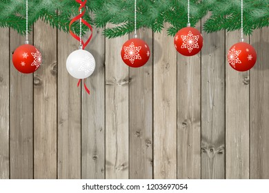 Christmas decoration, 4 red and 1 white balls on a brown wooden background