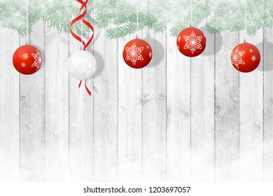 Christmas decoration, 4 red and 1 white balls on a white snowy wooden background