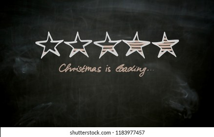 Christmas is loading concept painted on blackboard.