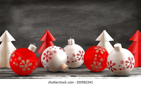 Christmas ornaments, balls, paper trees on a wooden table in front of a blackboard background. Copy space available.