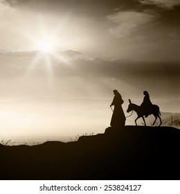 Christmas religious nativity concept: Joseph, Mary and baby Jesus with donkey on Bethlehem city