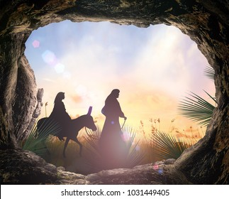 Christmas religious nativity concept: Tomb stone with palm leaves and Joseph, Mary on meadow sunset background