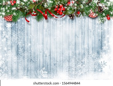 Christmas snow background with garland with candies, holly and b